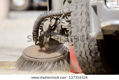 Detail of a road sweeper cleaning a market place. - stock photo