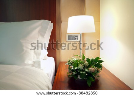 Detail of a room corner, lamp beside bed.