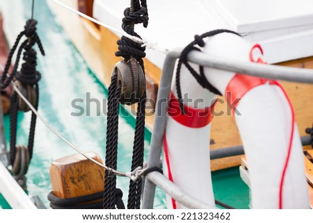 Detail of a sailing boat with lifebuoy, tackle, handrail and rope/Sailboat Details - stock photo