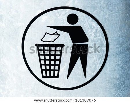 Detail of a signpost showing a figure throwing rubbish into a dustbin. - stock photo