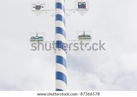 detail of a tree trunk in blue and white painted stripes, a so-called May pole. It is a traditional sign typical for Bavaria to indicate the range of workers and craftsmen in the area - stock photo