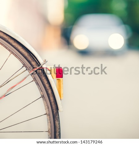 Detail of a Vintage Bike Back-light with Car Headlights in the Background - stock photo
