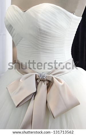 Detail of a wedding dress decorated with crystals, veils, ribbons and knot. - stock photo