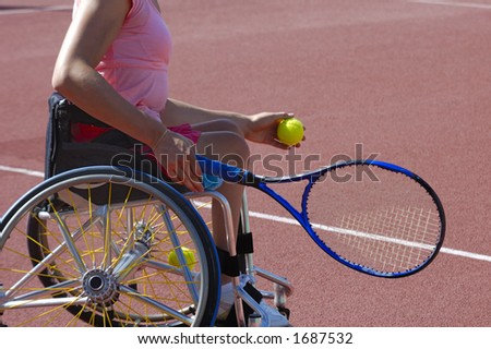 Detail of a wheelchair tennis player about to serve during a tennis championship match. Space for text on the plain area of the court behind her.