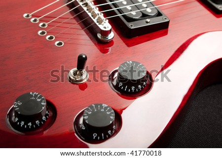 Detail of a wine red color electric guitar.