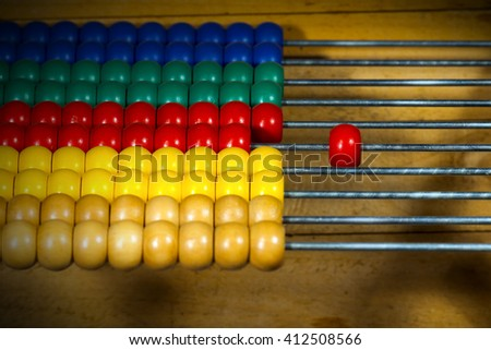 Detail of a wooden and colorful abacus on a brown background. Selective focus