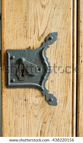 Detail of a wooden door with a handle, wrought iron handle