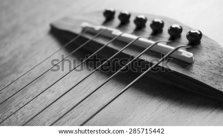 detail of acoustic guitar focus on  strings, very shallow depth of field. Black & White. - stock photo