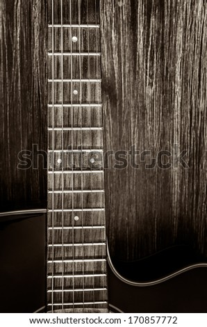 Detail of acoustic guitar in vintage style on wood texture background