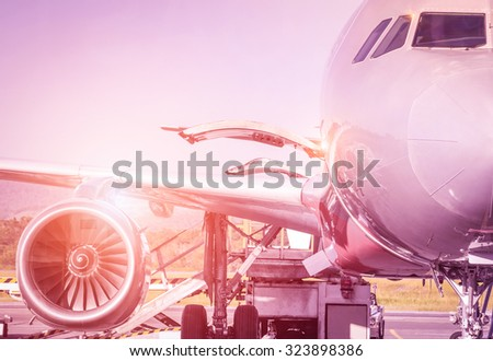 Detail of airplane at terminal gate before takeoff - Travel concept and wander around the world in international airport at sunset - Vintage marsala filtered look with sunshine halo  - stock photo