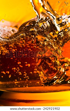 detail of an alcoholic beverage on yellow background - stock photo
