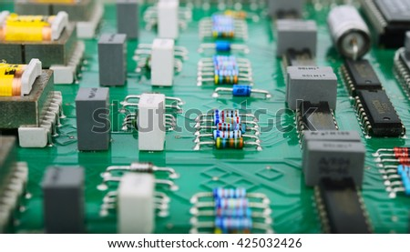 Detail of an electronic printed circuit board with many electrical components-(selective focus) - stock photo