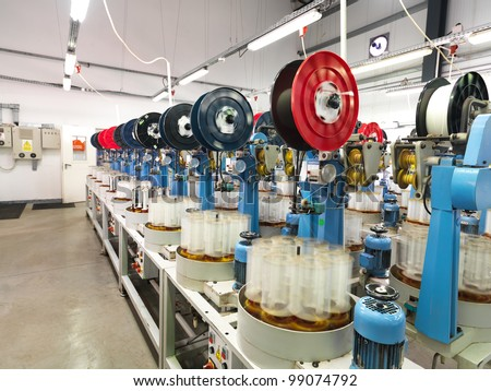 detail of an indoor industrial production line, in a thread factory - stock photo