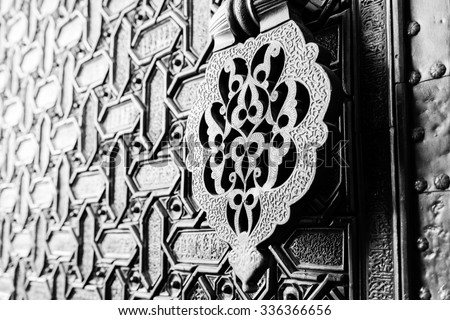 Detail of an islamic door knocker and ornaments outside one of the main entrance gates to the Cathedral of Seville, Spain. Shallow DOF, toned. - stock photo