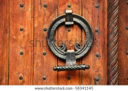 Detail of an massive ancient wooden door with iron knockers - stock photo