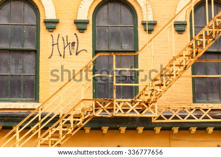 Detail of an old abandoned building with fire escape in downtown Cleveland's Flats district - stock photo