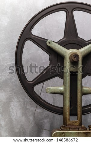 detail of an old and rusty cinema projector with film roll - stock photo