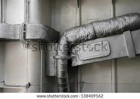Detail of an old exhaust pipe with asbestos cover.(Ship engine room) - stock photo