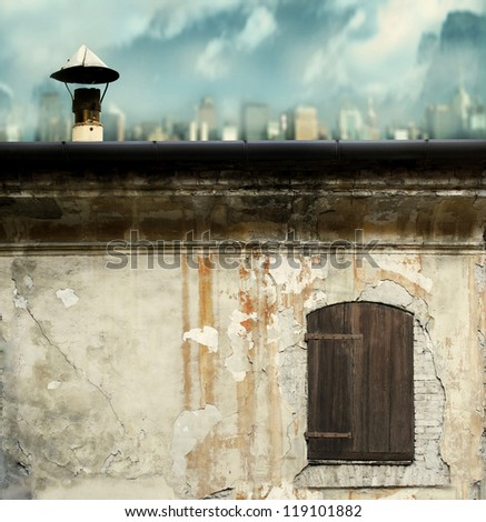 Detail of an old grungy facade and roof of a building with a city and cloudy sky on the background - stock photo