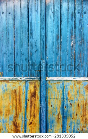 Detail of an old wooden door with scratched blue and yellow paint - stock photo