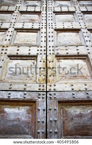 Detail of an old wooden doorway with metal nails reinforcement - stock photo