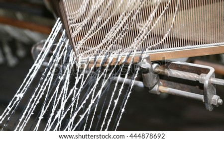 detail of ancient loom for the production of the fabrics in the textile industry - stock photo
