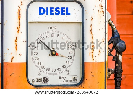 Detail of and old vintage diesel pump in orange and white. Handle at right side. Volume shown in liters on circular information board. - stock photo