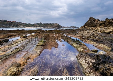 Detail of bare rocks because of low tide at Portio beach (Pielagos, Cantabria) - stock photo