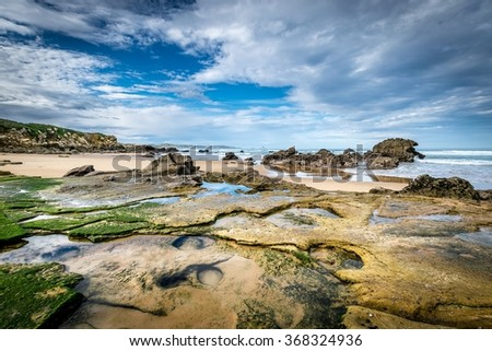 Detail of bare rocks because of low tide at Valdearenas beach (Liencres, Cantabria) - stock photo