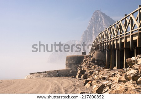 Detail of beach with old bunker and The Rock of Gibraltar on the background. La Linea de la Concepcion, Cadiz, Spain. - stock photo