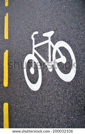 Detail of bicycle sign on asphalt road - stock photo