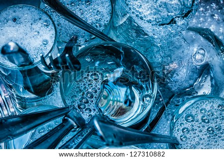 Detail of blue toned cutlery and glasses being washed with water and detergent