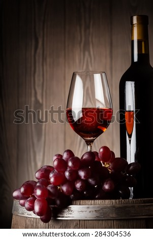 Detail of bottle and glass of red wine with grapes on old wooden barrel