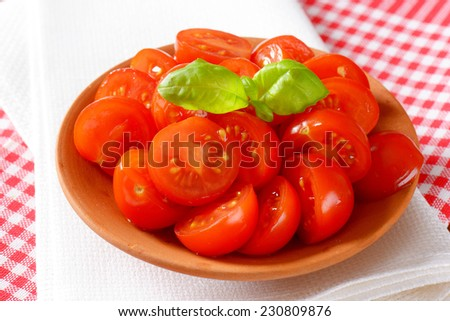 detail of bowl with halved cherry tomatoes with fresh basil - stock photo