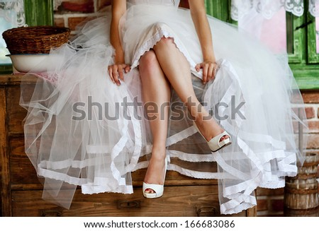 Detail of bridal legs with shoes sitting on the wooden table - stock photo