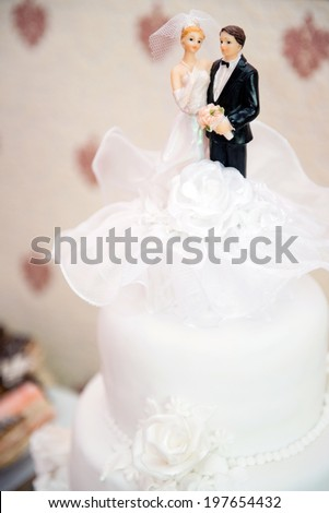 detail of bride and groom on a wedding cake - stock photo