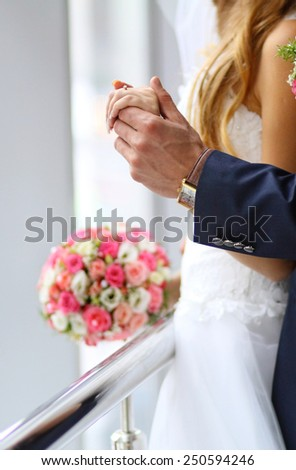 Detail of bride's roses bouquet and hands holding - stock photo