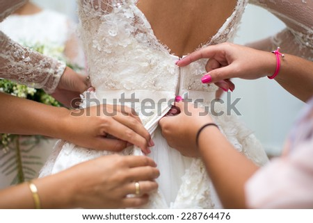 Detail of bridesmaid fixing bride's wedding dress - stock photo