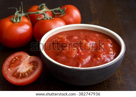 Detail of brown ceramic bowl of chopped tinned tomatoes on dark rustic wood surface. Surrounded with fresh tomatoes. - stock photo
