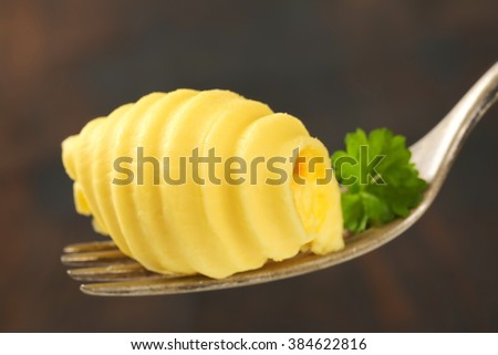 detail of butter curls and fresh parsley on metal fork