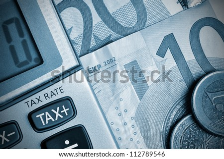 Detail of calculator, focusing the TAX key, next to some Euro bills and coins - stock photo