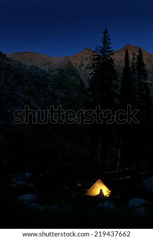 Detail of camping in glowing tent at night in mountains - stock photo