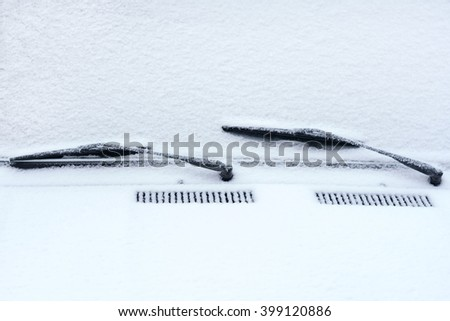 Detail of car windshield with snow-removing are covered with frost - stock photo