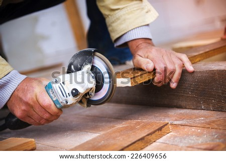 Detail of carpenters hand grinding wooden planks - stock photo