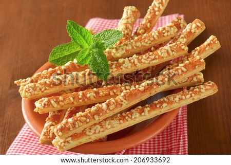 detail of cheese crunchy sticks, served in the bowl with patterned napkin - stock photo