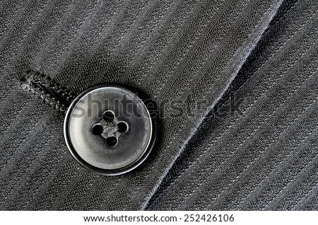 Detail of closeup of suit button on pin stripped cloth - stock photo