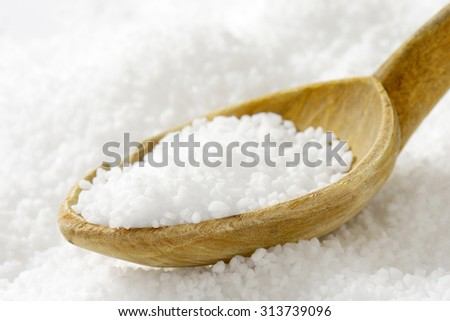 Detail of coarse grained salt and wooden spoon - stock photo
