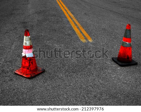 Detail of Construction Cones and yellow street lines suggesting repair - stock photo