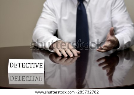 Detail of detective at desk with name sign hands - stock photo