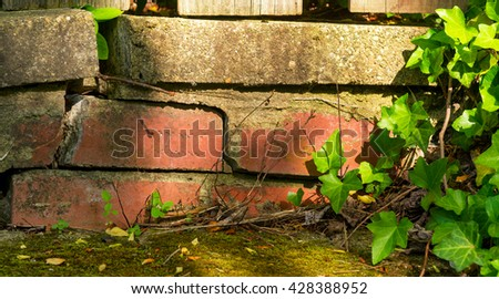 Detail of deteriorating brick work below a residential garden gate - stock photo